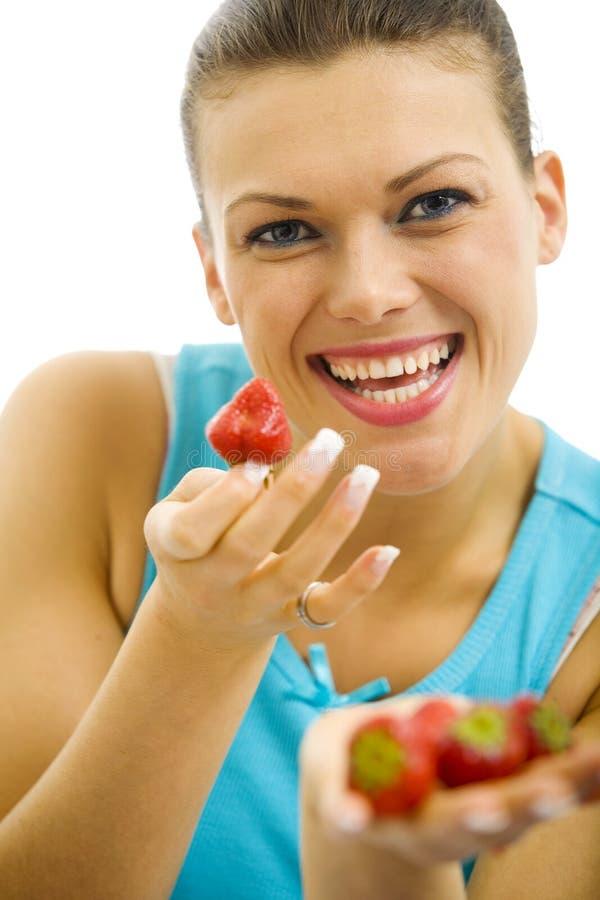 拿着一个新鲜的草莓的年轻俏丽的妇女 库存图片