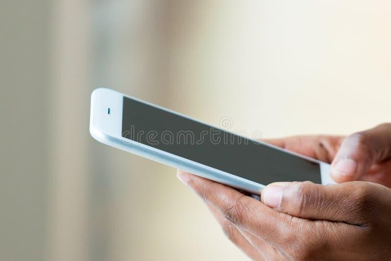 拿着一个有触觉的流动智能手机- Bl的非裔美国人的人 库存照片