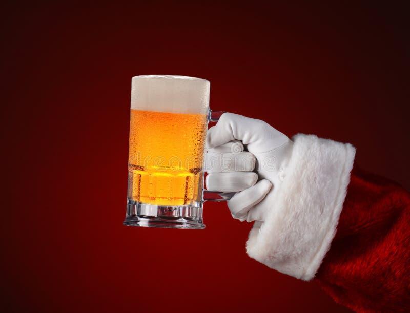 拿着一个杯子啤酒的圣诞老人 免版税库存照片