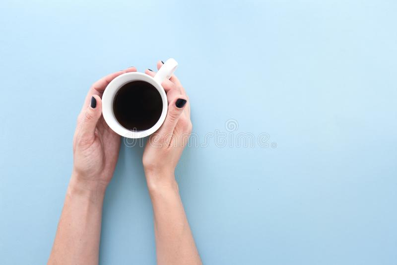 拿着一个杯子新近地煮的无奶咖啡的手,在蓝色背景平展放置 免版税图库摄影