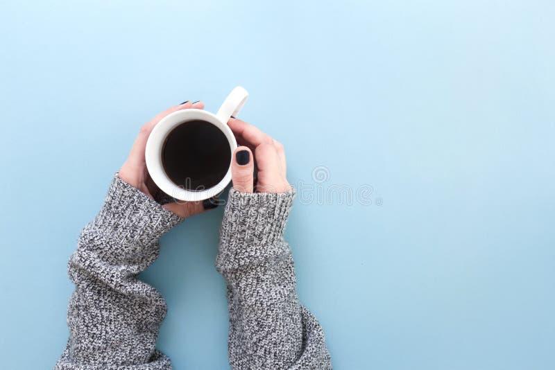 拿着一个杯子新近地煮的无奶咖啡的手,在蓝色背景平展放置 库存图片