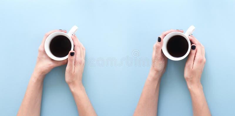 拿着一个杯子新近地煮的无奶咖啡的手,在蓝色背景平展放置 库存照片