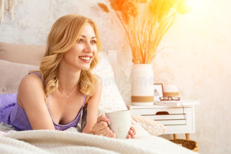 拿着一个杯子用茶或咖啡的少妇坐床在卧室 在谎言毛线和编织针附近 免版税库存照片