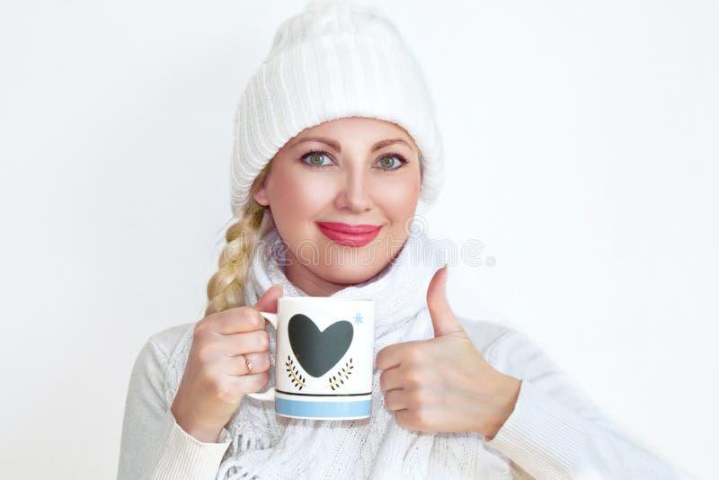 拿着一个杯子茶和显示她的赞许的一条被编织的帽子和围巾的一个少妇 免版税库存照片