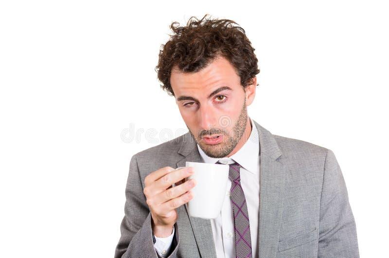 拿着一个杯子饮料的一个疲乏的困商人 免版税图库摄影