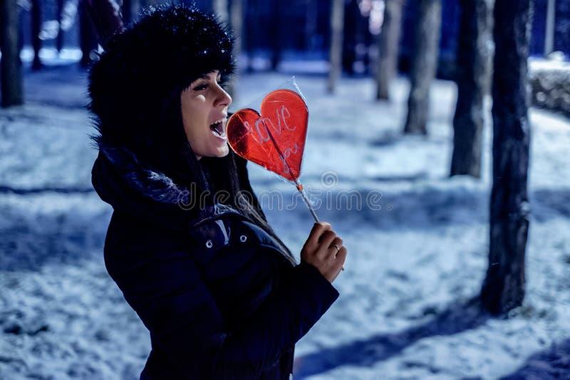 拿着一个棒棒糖的女孩在一个多雪的公园 免版税库存照片