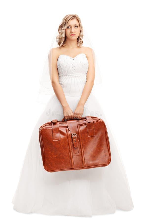 拿着一个棕色手提箱的失望的新娘 免版税库存照片