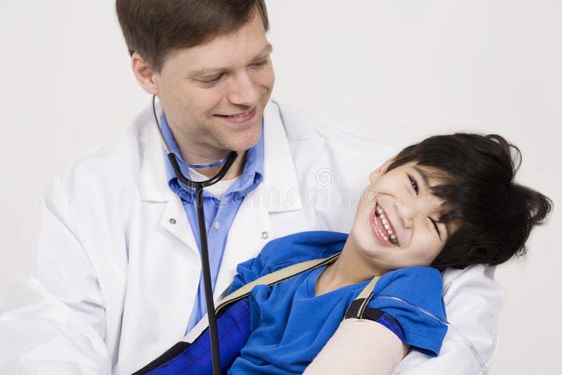 拿着一个残疾小男孩的医生 库存照片