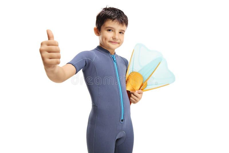 拿着一个潜水的面具和显示赞许的保温潜水服的男孩 免版税图库摄影