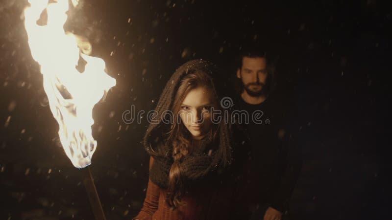 拿着一个火炬的一对年轻神秘的夫妇的画象在黑暗的森林里