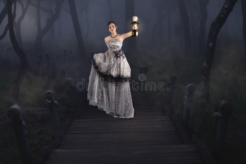 拿着一个灯笼的美丽的女孩在森林 免版税库存图片