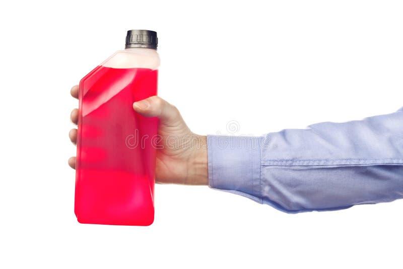 拿着一个瓶不冻液的手 库存图片
