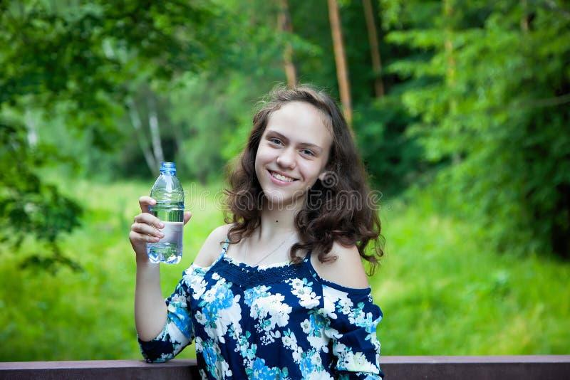 拿着一个瓶凉快的饮用水的一个美丽的微笑的青少年女孩的画象在夏天绿色公园 图库摄影