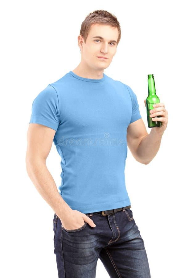 拿着一个瓶啤酒的新英俊的人 免版税库存图片