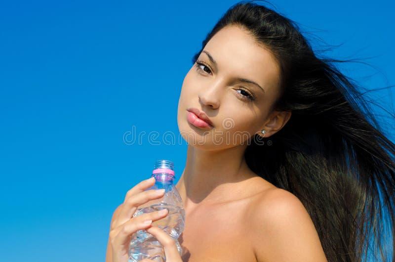拿着一个瓶水的美丽的深色的女孩 免版税库存图片
