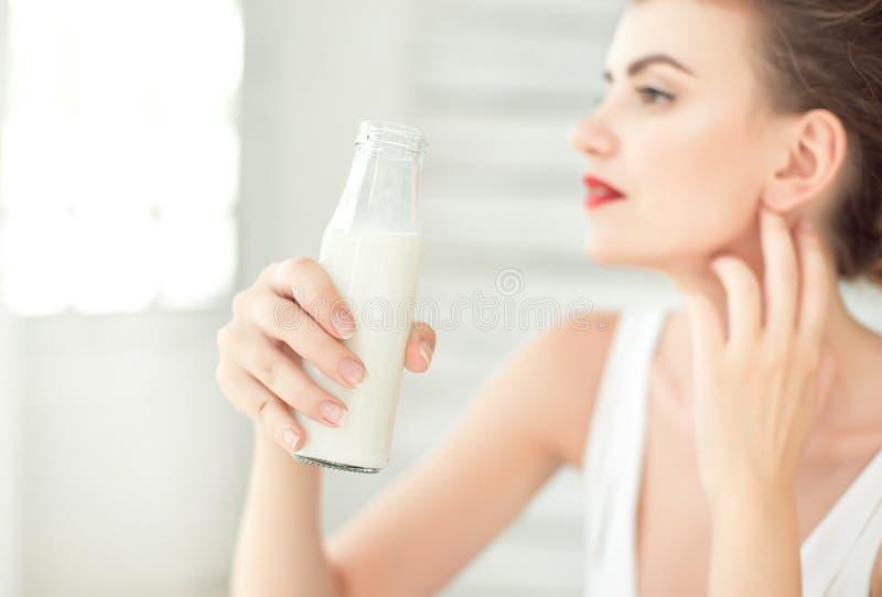 拿着一个瓶牛奶的少妇在她的手上 套深色的女孩佩带的白色汗衫在有窗口的绝尘室 库存照片