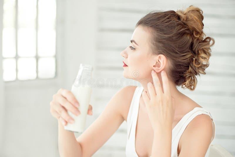 拿着一个瓶牛奶的少妇在她的手上 套深色的女孩佩带的白色汗衫在有窗口的绝尘室 图库摄影