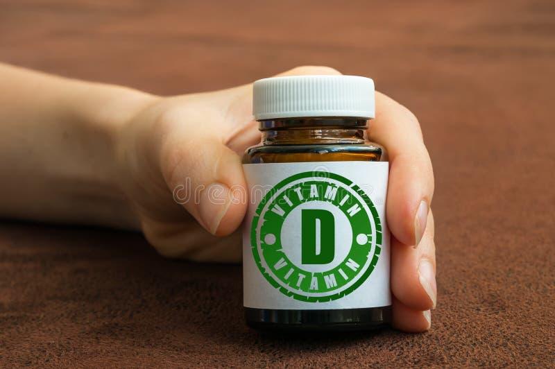 拿着一个瓶药片的人的手用维生素D 免版税库存照片