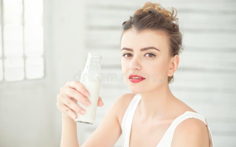 拿着一个瓶豆奶的年轻深色的妇女在她的坐在一间明亮的屋子的手上 概念健康生活方式 库存照片