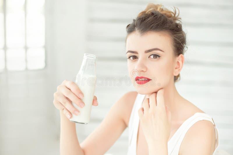 拿着一个瓶豆奶的年轻深色的妇女在她的坐在一间明亮的屋子的手上 概念健康生活方式 免版税库存照片