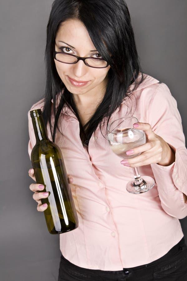 拿着一个瓶酒和a的美丽的性感的女孩 免版税库存图片