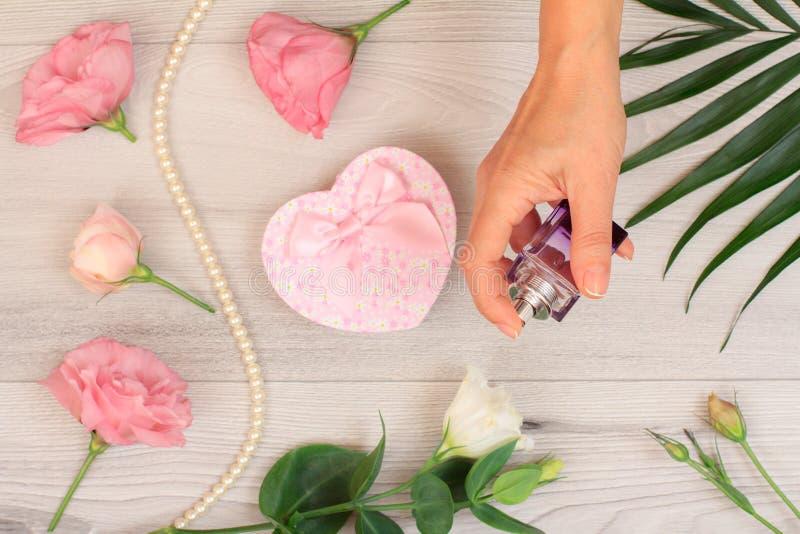 拿着一个瓶香水的妇女在手上有在背景的花的 免版税库存照片
