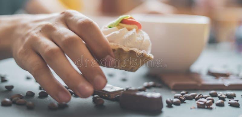 拿着一个甜蛋糕和一杯咖啡在黑暗的桌上的接近的手早晨f 免版税库存图片
