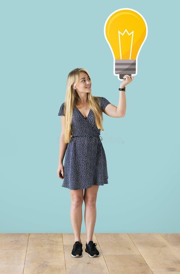 拿着一个电灯泡象的妇女 免版税库存图片