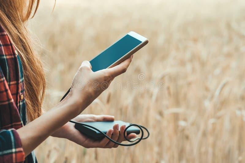 拿着一个电话和充电它从力量银行的一个黄色领域的女孩在她的手上 免版税库存照片