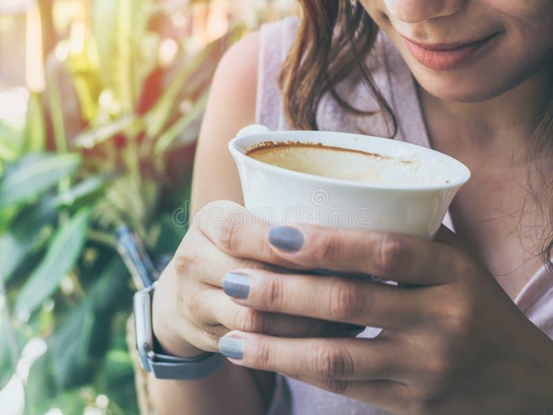 拿着一个白热咖啡杯的妇女手 库存照片