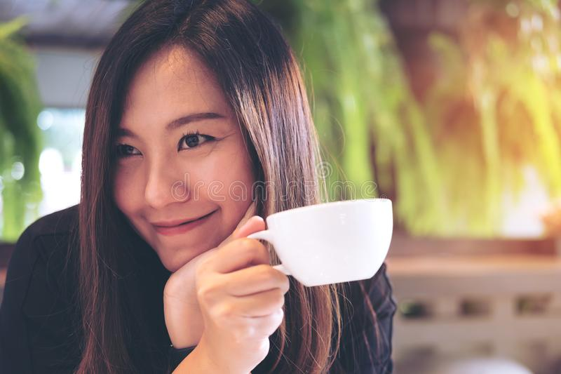 拿着一个白色杯子和喝与感到的一名美丽的亚裔妇女热的咖啡愉快在现代咖啡馆和绿色自然背景 免版税库存图片