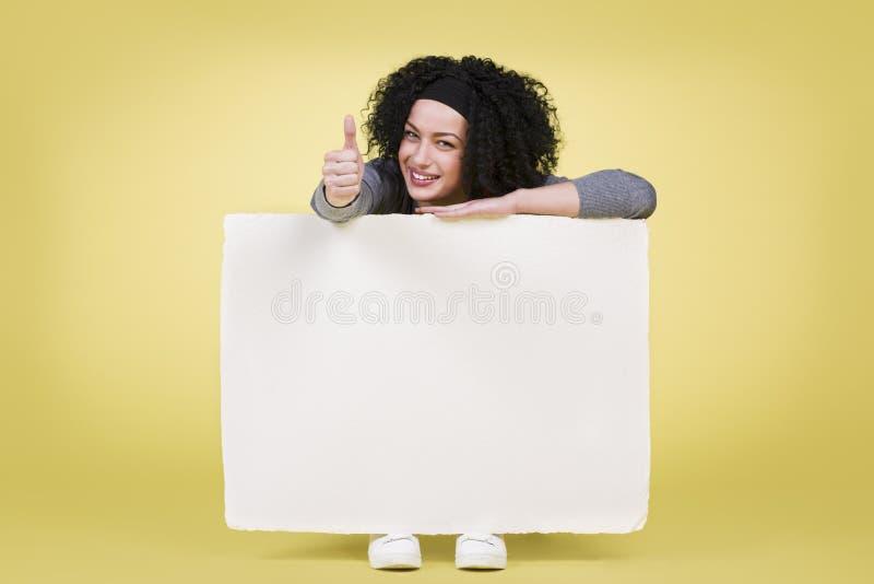 拿着一个白色标志的微笑的妇女上显示赞许 免版税库存照片