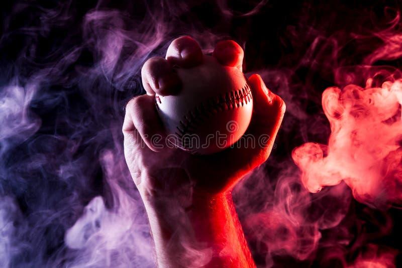 拿着一个白色棒球球的一只强的男性手的特写镜头 免版税库存照片