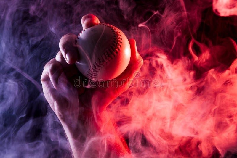 拿着一个白色棒球球的一只强的男性手的特写镜头 免版税图库摄影