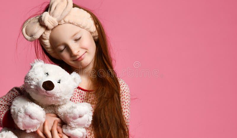 拿着一个白色玩具熊的微笑的女婴在屋子里一个桃红色背景 库存照片