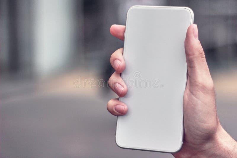 拿着一个白色电话的年轻人,不用在一个被弄脏的城市的背景的商标 免版税库存图片