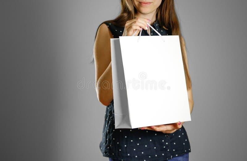 拿着一个白色礼物袋子的女孩 免版税库存照片