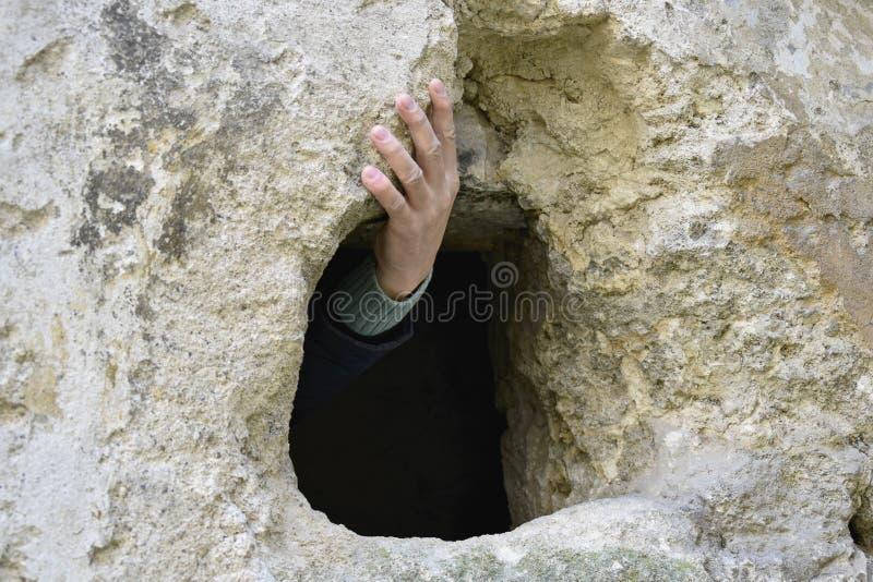 拿着一个石壁架的人的手 秘密通道 免版税库存照片