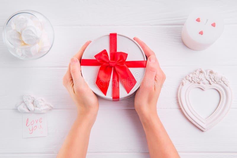 拿着一个礼物的女性手为华伦泰` s天 充满爱的卡片您handwrite词、甜点、蜡烛和框架在形状听见 库存图片