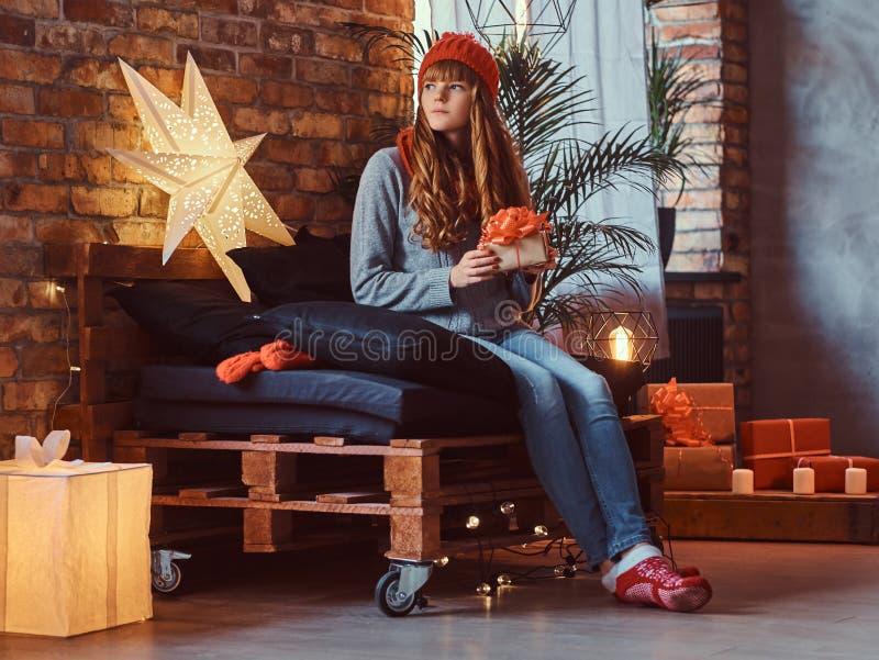 拿着一个礼物盒的红头发人女孩在一个装饰的客厅在圣诞节打过工 图库摄影