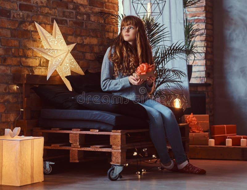 拿着一个礼物盒的红头发人女孩在一个装饰的客厅在圣诞节打过工 免版税库存照片