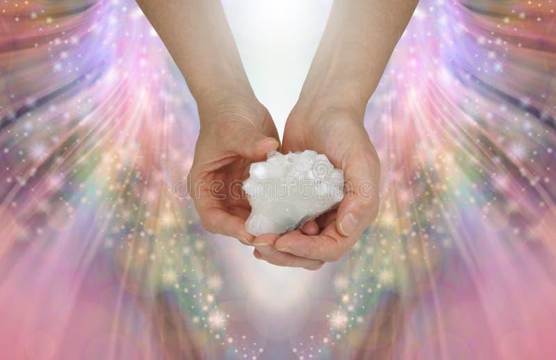 拿着一个神圣的发怒水晶标本 免版税库存照片
