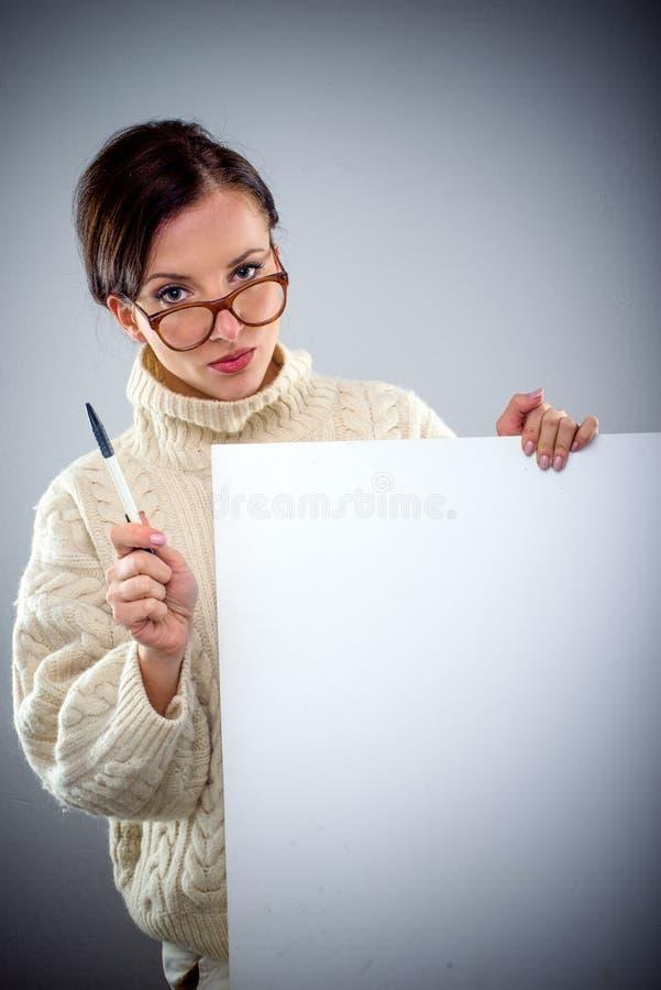 拿着一个空白的标志的严肃的可爱的妇女 免版税库存图片