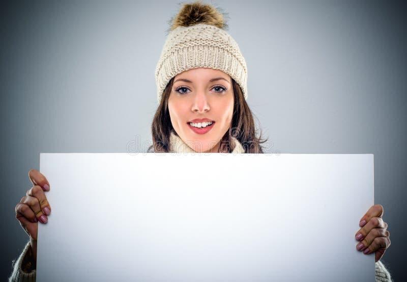 拿着一个空白的标志的华美的少妇 免版税库存照片