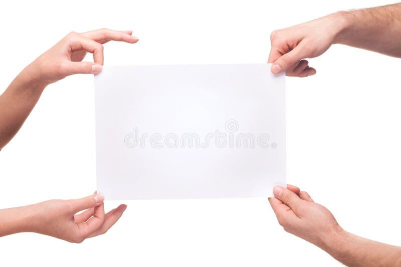 拿着一个空白的白板的四只手 免版税图库摄影