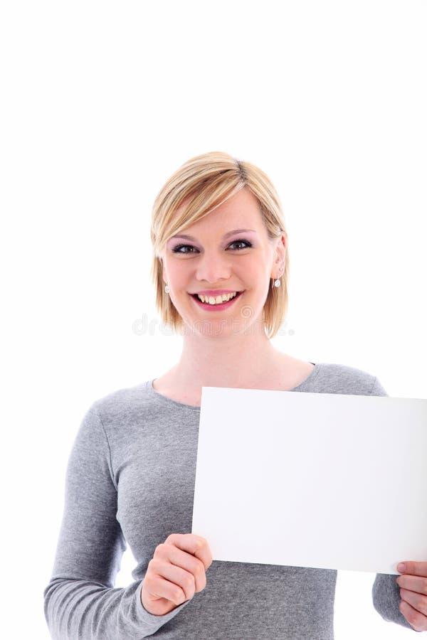 拿着一个空白符号的友好妇女 库存照片