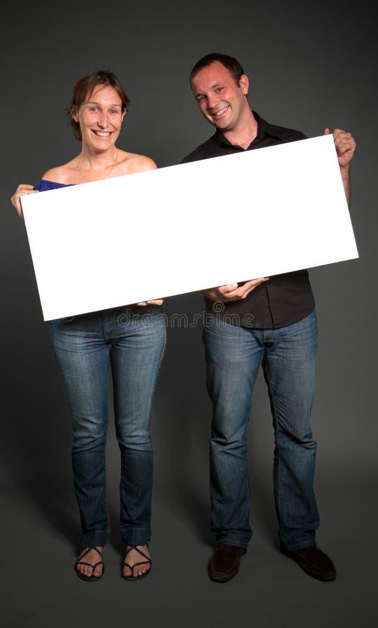 拿着一个空白符号的夫妇 免版税库存照片