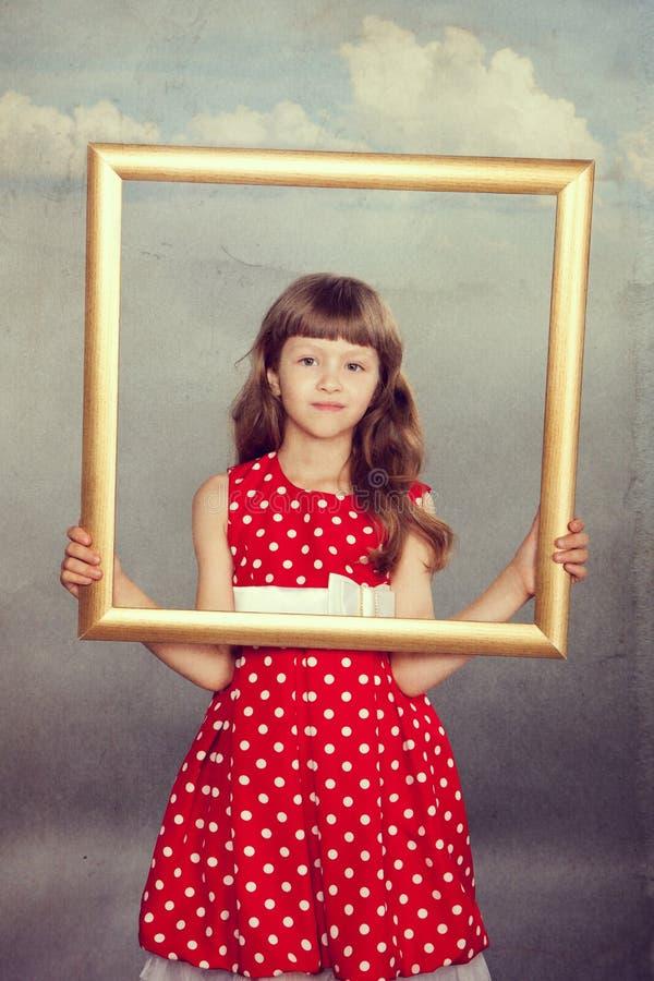 拿着一个空的框架的美丽的女孩 免版税图库摄影