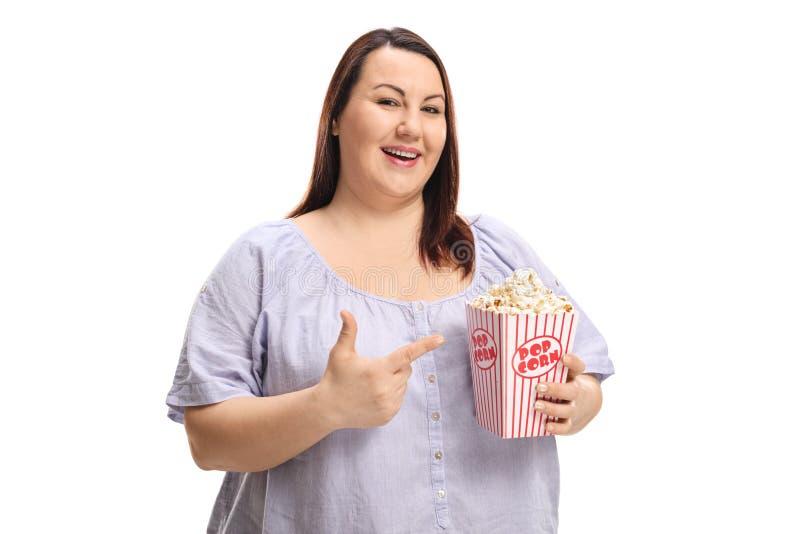 拿着一个箱子用玉米花和指向的肥头大耳的年轻女人 免版税库存图片