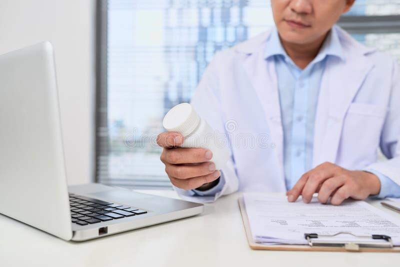 拿着一个箱子药片的男性医生在医疗办公室 免版税库存照片